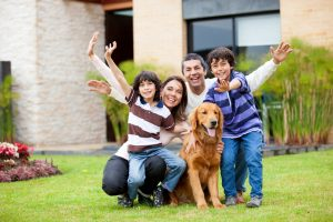 Happy family with a dog outside their house
